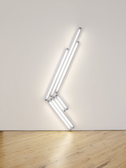 Seven fluorescent-white, tubular lights positioned against a white wall and placed at an angle, four of which are shorter bulbs slanted toward the floor and three of which are longer bulbs slanted upward.