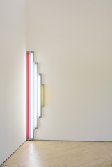 White, red, and yellow fluorescent tubes are mounted at the intersection of two walls.