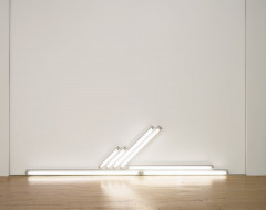 Several white fluorescent tubes sit on the floor and others are mounted horizontally on the wall.