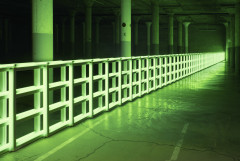 A green fluorescent barrier spans a large dark room with pillars.