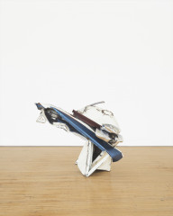 A squat, angular sculpture made of white and blue metal parts rests on a wooden floor.