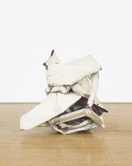 A crumpled-and-folded, white, metallic object with red details rests on a wooden floor in front of a white background.