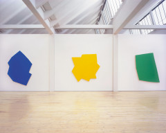 Three large wall-mounted polygons in different, irregular shapes, one bright blue, one yellow, and one green.