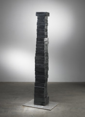 A stack of twenty-seven bronze blocks of different sizes rests above a thin stainless-steel platform.