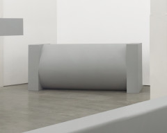 A large, cylindrical, gray sculpture lies lengthwise between two large, rectangular, gray ends.