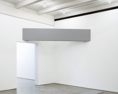 A horizontally oriented, rectangular, gray beam is suspended in front of a corner and above a door to its left.