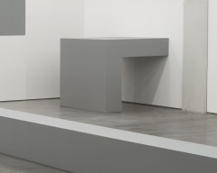 A right-angle-shaped, gray sculpture is installed against a wall.