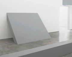 A thick, rectangular, gray sculpture leans against wall.