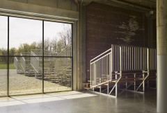 Outdoor bleachers on gravel are framed by a large glass window, while another set sit inside a large sunlit industrial space.