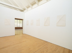 Six sheets of creased paper are evenly spaced along the horizon of two white walls and an open doorway.