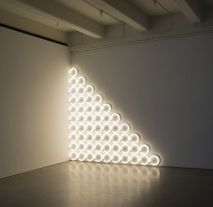 A triangle composed of white fluorescent circular tubes is placed on a white wall.