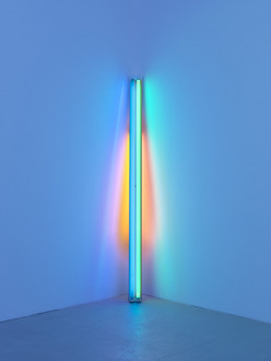 A blue fluorescent tube leans on the corner of a wall, reflecting red and orange tones behind it.