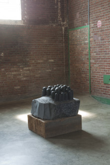 A dark sculpture with domed cylinders sprouting from its base on top of a solid slab of wood.