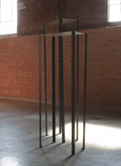 Two rectangular metal sheets lie flat across the tops of eight vertical metal poles.