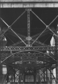 Black-and-white photograph of metallic vertical, diagonal, and horizontal trusses and arches across a space.