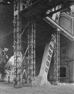 Black-and-white photograph of a vertical and diagonal metal support structure in front of a brick building.