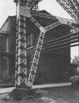 Black-and-white photograph of a brick building behind a massive set of intersecting vertical and diagonal metal trusses and four metal pipes suspended from the building in mid-air.