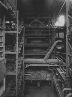 Black-and-white photograph of a multilevel factory interior with platforms, staircases, railings, and a metal support structure surrounding a blast furnace.
