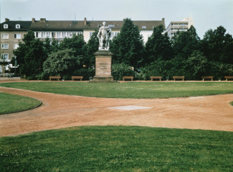 A grassy park featuring four red-dirt paths that intersect at a square silver plate flush to the ground.