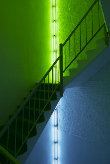 Two fluorescent artworks in corners on two floors of a stairwell, the lower piece is blue and the upper piece is green.