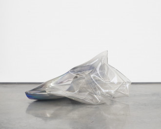 A folded, cone-shaped, iridescent, glass object rests on a reflective, cement surface in front of a white background.