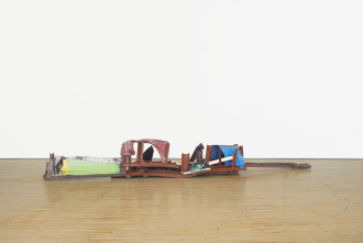 A long, low-lying sculpture made of red, blue, green, and white metal parts rests on a wooden floor.