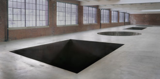 A cement floor featuring cutouts in the shape of a square, a circle, and a rectangle spanning the length a large room.