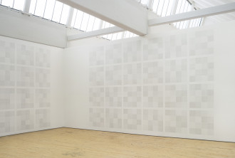 Two grids of drawings of squares within squares covering the space of two white walls.