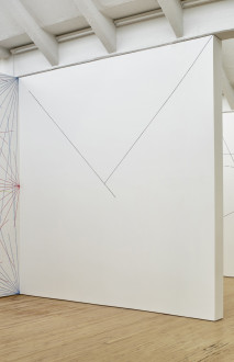 A large drawing featuring two diagonal lines from the top corners joining and forming a trianglular shape covers a wall.