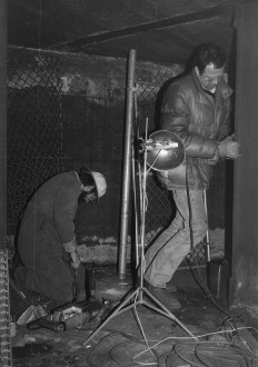 Two men are working with tools in an enclosed dark space in this black-and-white image.