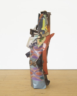 A vertically oriented sculpture made of multicolored metal parts rests on a wooden floor.