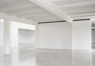 A yellow thread is suspended from the ceiling and runs along the floor, creating a triangle in a white industrial space. A second work in dark thread is partially visible farther into the background.