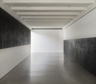 Two parallel walls are painted half black and half white, with black above white on the left wall, and white above black on the right wall, both extending toward but not conjoined by a perpendicular white wall.