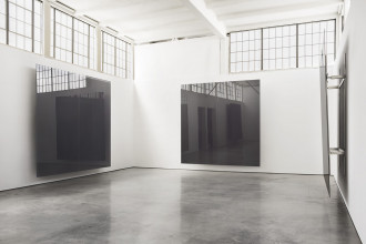 Three large reflective planes of gray sheet glass each mounted to a different white wall in large sunlit room with a polished concrete floor and windows.