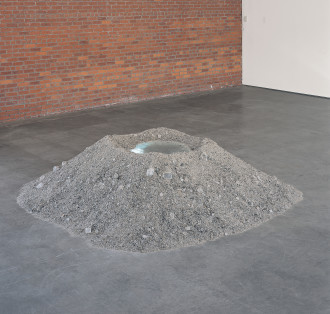 A large, pyramid-shaped pile of gray salt with a mirror inset on top.