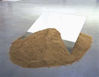 A mound of sand on a concrete floor with a rectangular mirror sticking out of it.