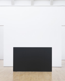 A wall-like, rectangular, dark sculpture with two vertical seams is centered on a wooden floor in front of a square white wall.