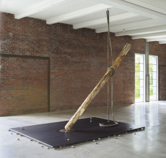 A long wooden log hangs from a thick rope above a large rectangular steel plate with small rocks sandwiched between the plate and concrete floor.