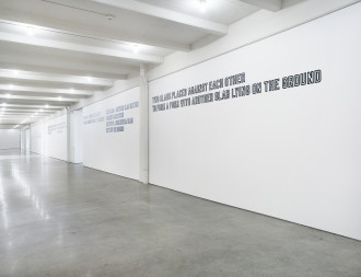 Three gallery walls along a corridor feature white text outlined in black. The nearest text reads: