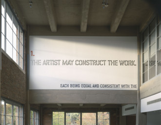 Orange, gray, and blue text outlined in black placed high on a wall in a double-height industrial room. The text reads,