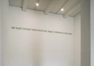 Green stenciled text placed high on a white wall reads:
