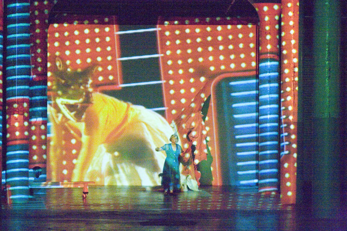 A woman wearing a blue dress stands in front of a screen with projected images of a large cat and red-and-blue shapes.