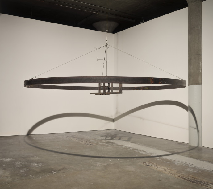 A metal chair in the center of a large circular band, both suspended in an industrial space with concrete floor and white walls onto which the object casts a prominent shadow.
