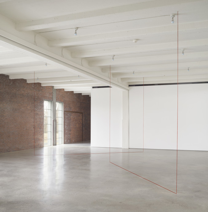 Red thread is suspended from the ceiling and runs along the floor at 90-degree angles in an industrial space.