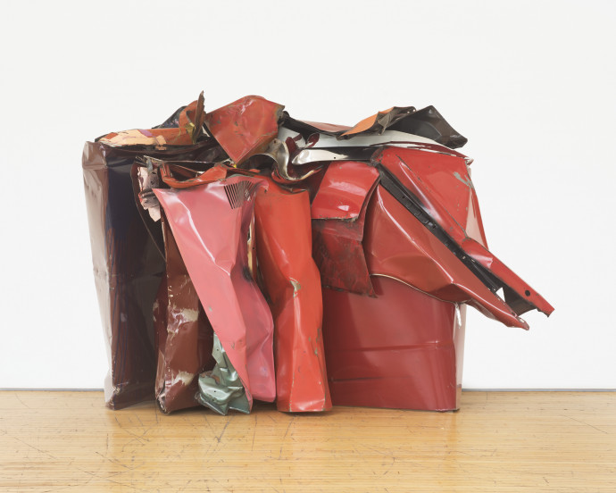 A crumpled-and-folded metallic object in white, brown, silver, and various shades of red rests on a wooden floor in front of a white background.